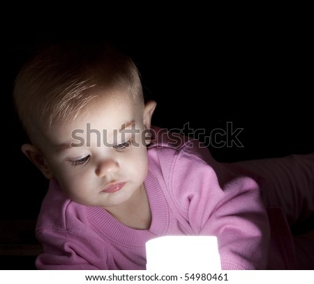 Baby lying on the ground,  playing with a light. Concept of the future of our energy. - stock photo