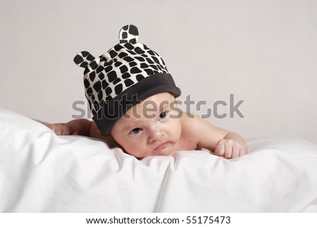 baby lying on the pillow in in white for black hat with ears - stock photo