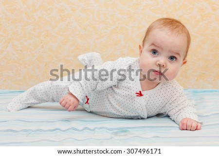 Baby lying on tummy and trying to crawl. Baby looking straight at the camera. Selective focus on baby head. - stock photo