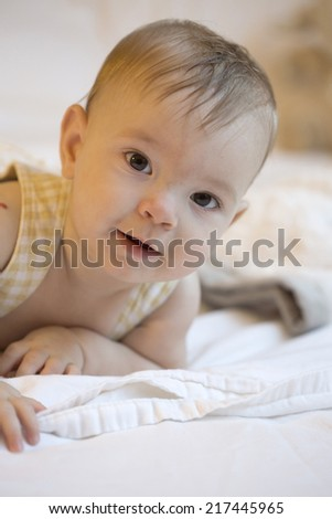 baby lying on white sheets, looking at camera