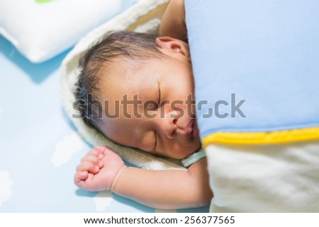 Baby lying under a blanket on the futon. - stock photo