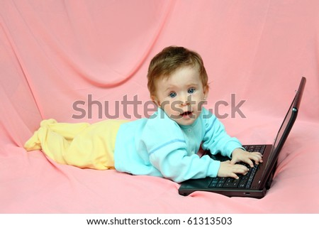 baby lying with laptop on pink background - stock photo