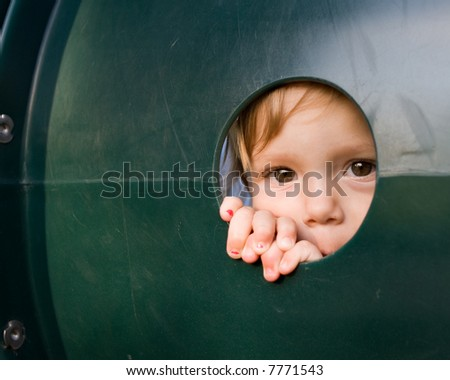 Baby making direct eye contact, peeping out of a portal in plastic playground equipment. - stock photo