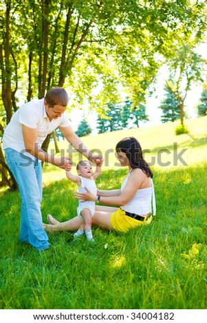 Baby making first steps with the help of his parents - stock photo