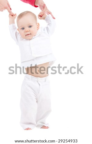 Baby making his first steps in life with mom hands helping him - stock photo