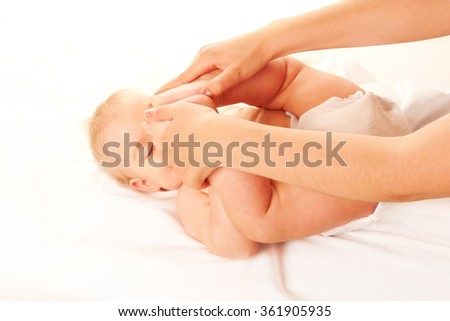 Baby massage. Mother baby feet touching his forehead. Isolated on white background - stock photo
