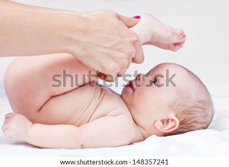 Baby massage. Mother massaging baby's legs. Isolated on white background - stock photo