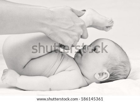 Baby massage. Mother massaging baby's legs. Isolated on white background ( black and white ) - stock photo