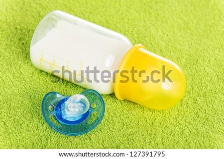 Baby milk bottle and dummy close up - stock photo
