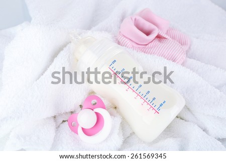 Baby milk bottle, pacifier and babys bootees on towel - stock photo