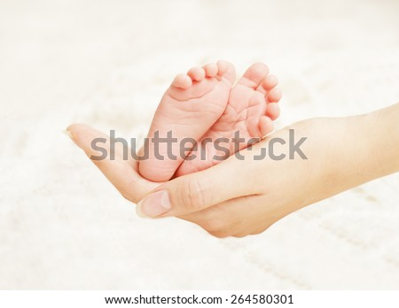 Baby Newborn Feet in Mother Hands. New Born Kid Foot, Family Love Concept - stock photo