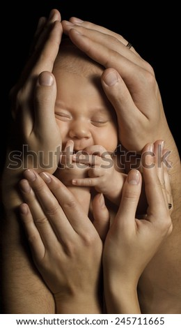 Baby Newborn in Parents Hands Sleeping. Family Concept. Child Birth. Black Background.  - stock photo