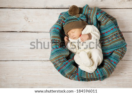 baby newborn sleeping in woolen hat, new born on white wooden background, warm winter country style - stock photo