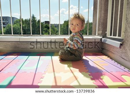 baby on a balcony sitting on alphabet foam carpet - stock photo