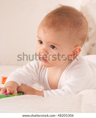 Baby on a bed playing with plastic brick toys - stock photo
