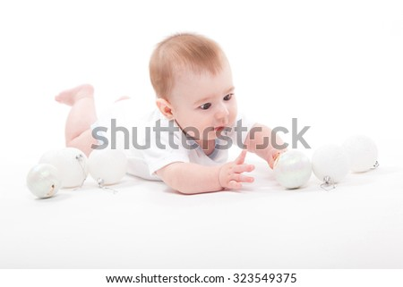 baby on a white background playing with Christmas toys, picture with depth of field