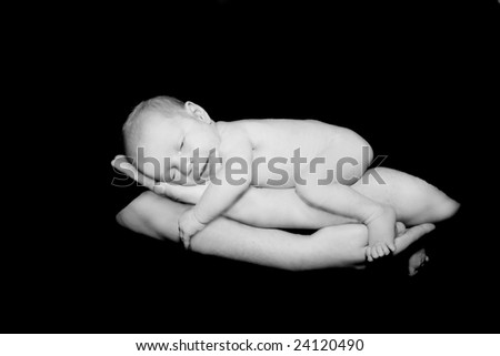 baby on father's hands over black