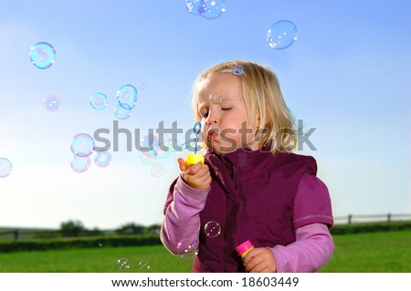 Baby on green meadow with bubble