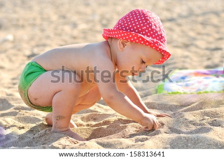 baby on the beach playing with sand
