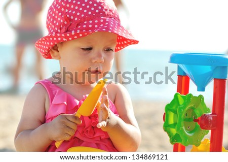 baby on the beach playing with toys - stock photo
