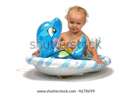 baby on the beach with a swimming toy - stock photo
