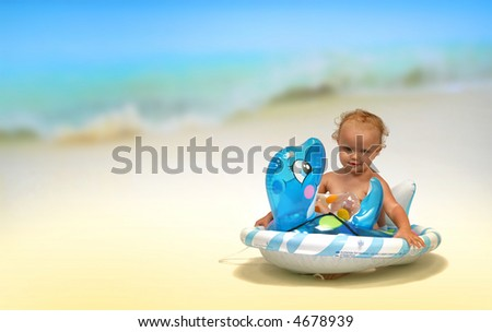 baby on the beach with a swimming toy