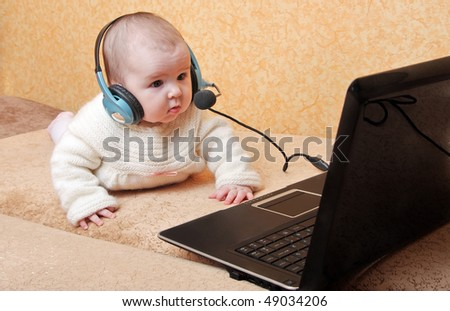 Baby on the couch for a laptop in headset - stock photo