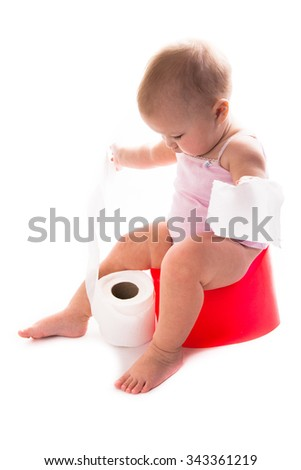 baby on the pot, the baby pissing on a pot of red, white background,tearing toilet paper - stock photo