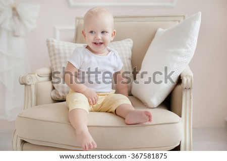baby one year old sitting in a chair in the bedroom - stock photo