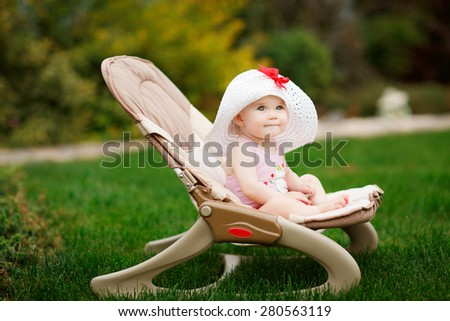 Baby or a toddler child relaxing on a sunbed or a deck chair in a garden.
