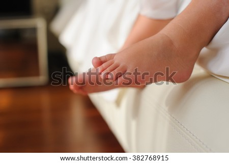 Baby or Children foot  sitting on the white bed, closeup. - stock photo