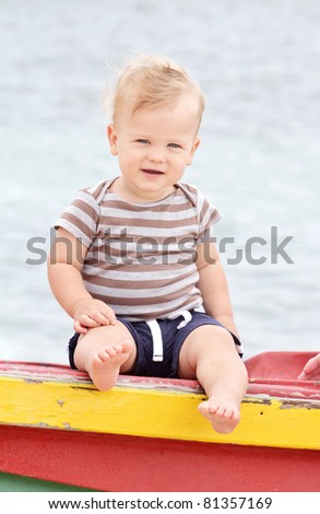 Baby or toddler boy sitting on a colorful tropical boat against the ocean