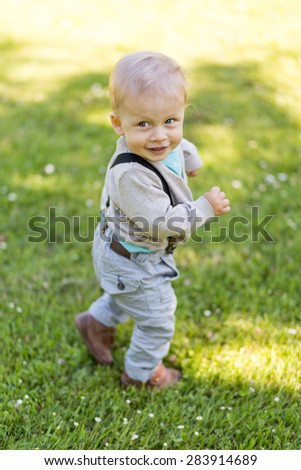 Baby outdoors running and playing on the grass. - stock photo