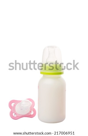 Baby pacifier and a bottle of baby formula milk over white background - stock photo