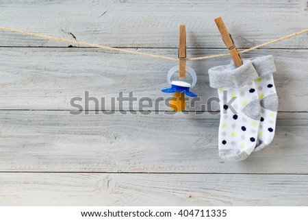 Baby pacifier and socks hanging on clothesline on wooden background - stock photo