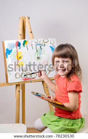 Baby paints at the easel painting - stock photo