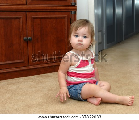 Baby pauses as she faces her fears of the dark hallway in her home.  Denim shorts and summer top with bare pink painted toenails. - stock photo