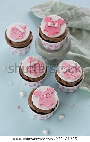 Baby pink fondant chocolate cupcakes on light blue background. Baby girl shower party cupcakes. - stock photo