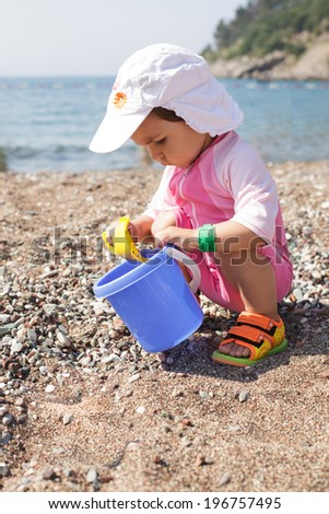 Baby play on seashore with rebbles and pail - stock photo