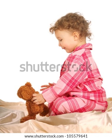 baby playing  bear playing on white bed - stock photo