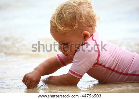 baby playing in the sand with her fingers
