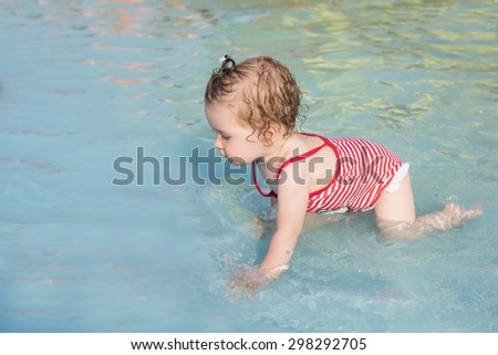 Baby playing in the swimming pool for the first time - stock photo