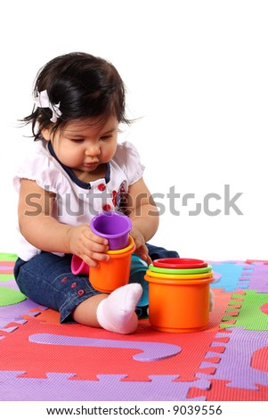 Baby playing on a colorful alphabet mat - stock photo