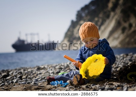 Baby playing on sea shore with a huge boat in the background - stock photo
