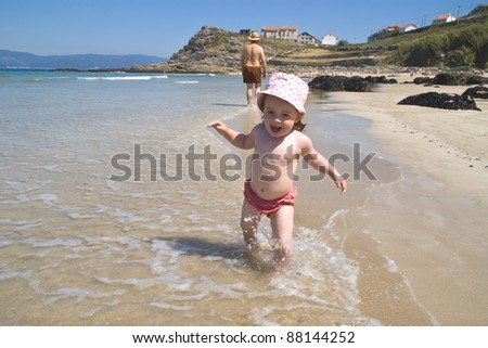 baby playing on the beach.