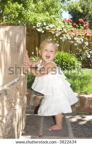 Baby Playing Peek A Boo In Garden - stock photo