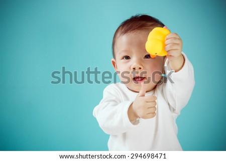 Baby playing rubber duck - stock photo