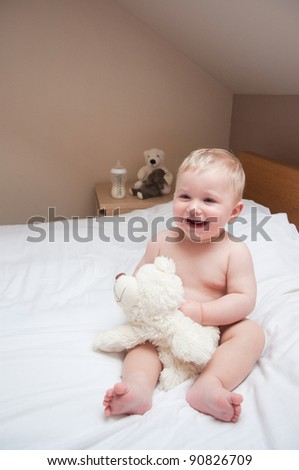 baby playing teddy bear playing on white bed
