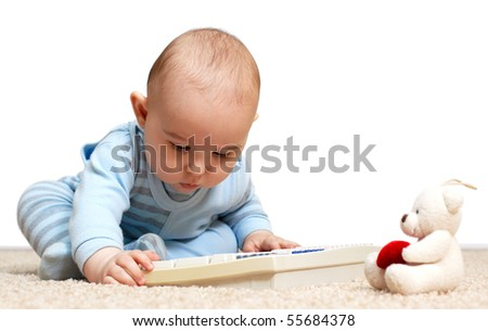 Baby playing with a keyboard. Isolated over white background - stock photo