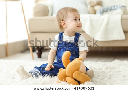 Baby playing with a toy bear on the floor - stock photo